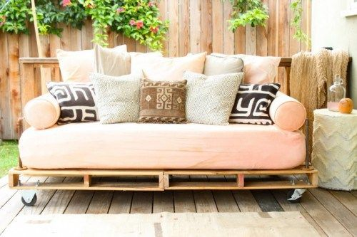 Sofá de palés con cojín en rosa