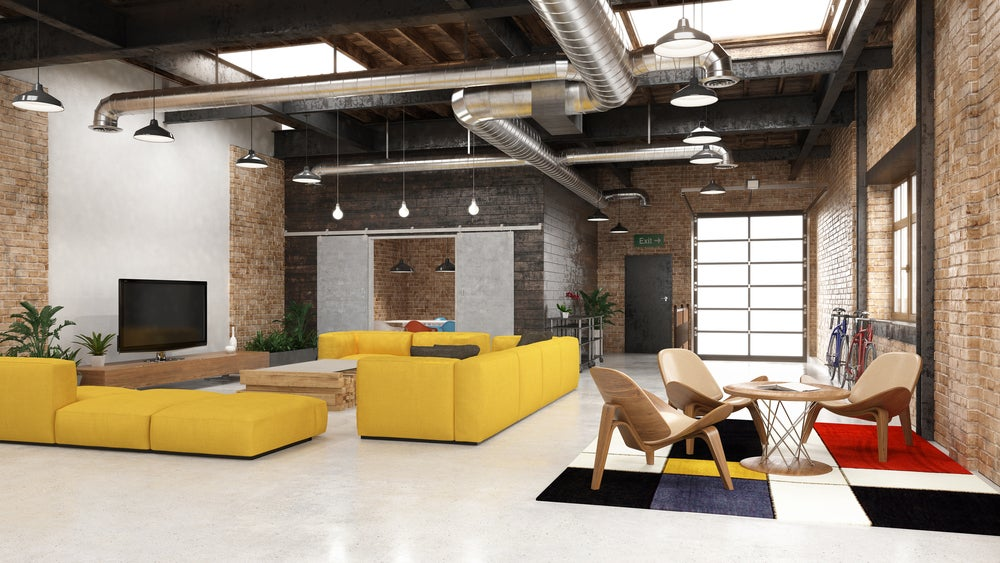 Estilo industrial con paredes de ladrillo y tuberías visiibles.