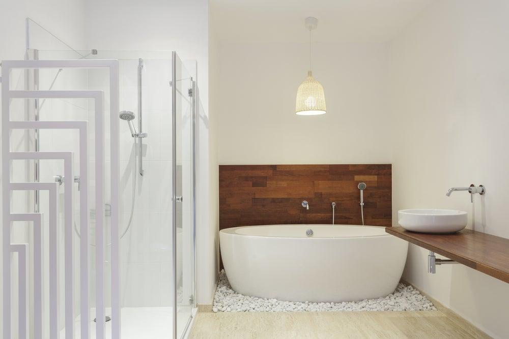 Cuarto de baño con la pared de la bañera y la encimera del lavabo en madera oscura