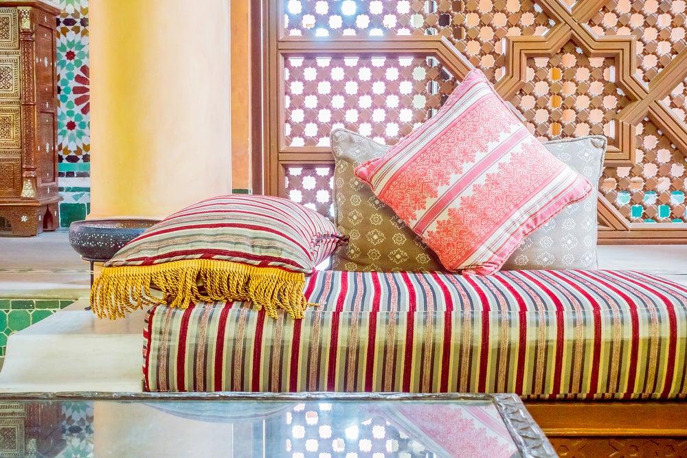 Decoración marroquí con telas de colores y celosía de fondo