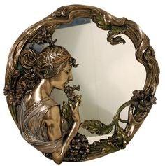 Espejo con acabado dorado con marco vegetal y figura femenina