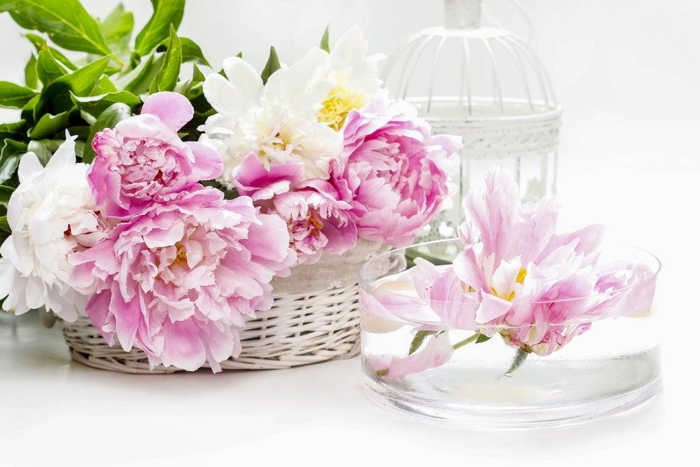 Varias flores colocadas en una cesta de mimbre blanca