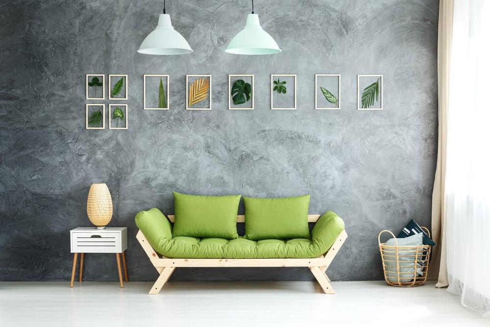 Habitación de estilo tropical sutil: cuadros con plantas, sofá de madera con cojines en verde, cesta de mimbre