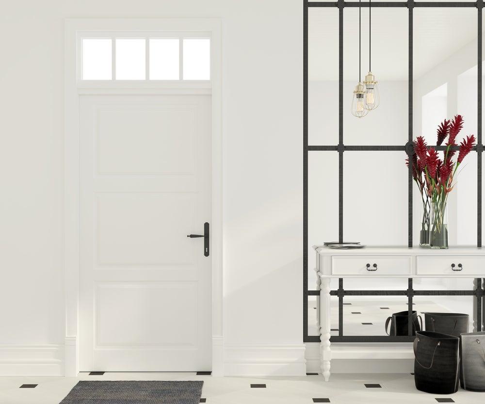 Recibidor estilo minimalista con una mesa en blanco y un espejo grande