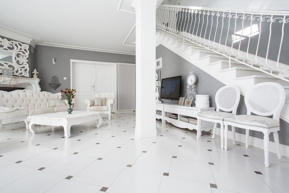 Salón decorado con estilo decimonónico en tonos blancos