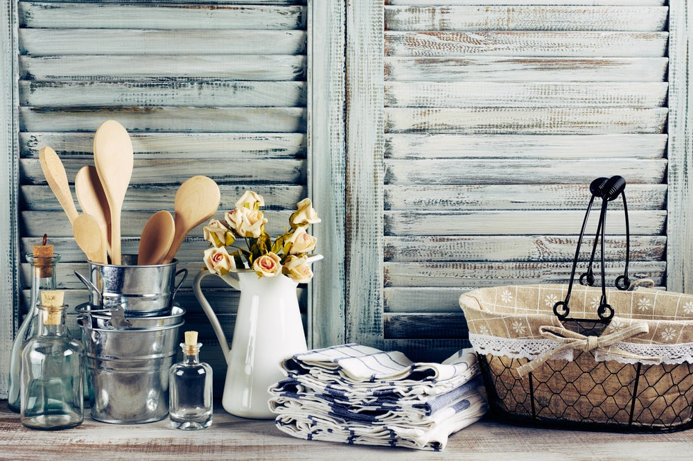 Elementos de época vintage para decorar tu cocina de madera: cesto, jarrón con flores, manteles, cucharones de madera.