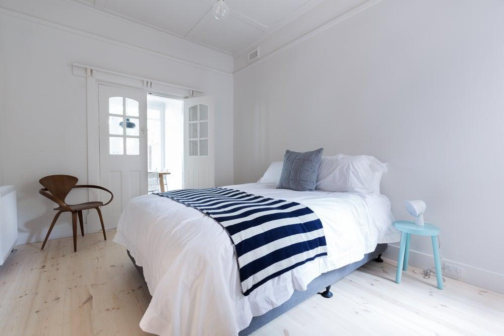 Habitación básica para invitados decorada al estilo nórdico en blanco con detalles azules.