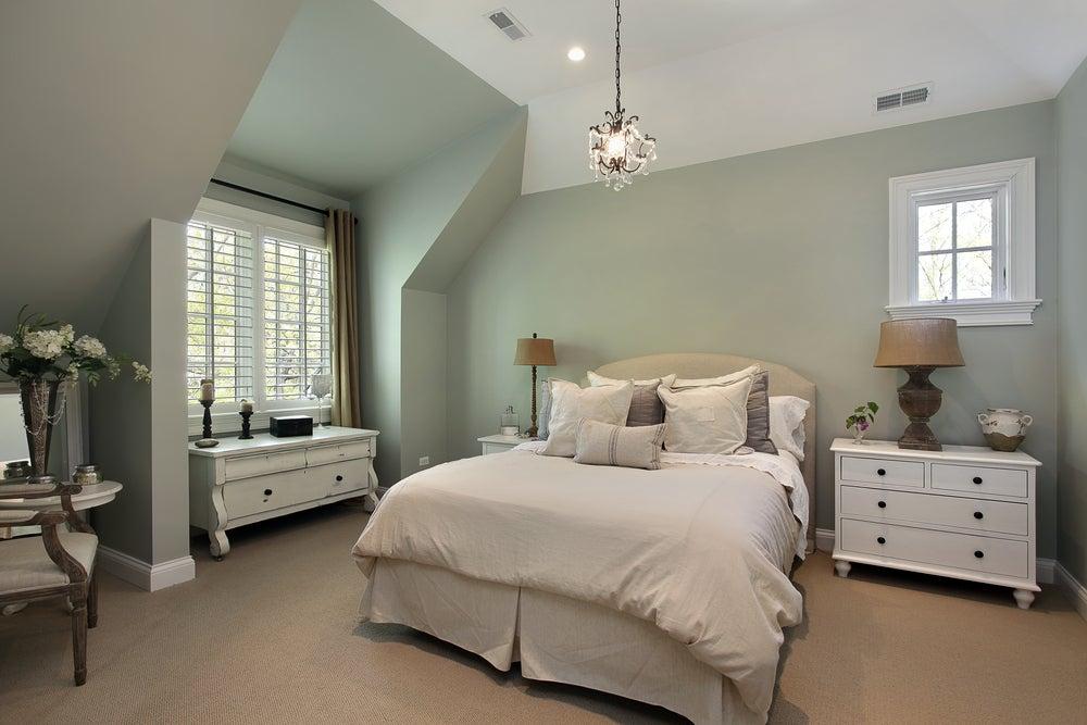 Habitación para invitados: lámparas en las mesillas, armario, pie de cama con toallas.