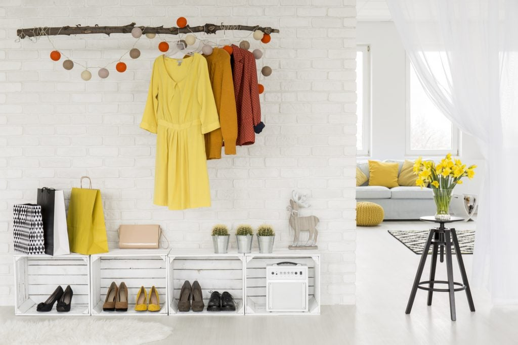 Hall con zapatero a modo de estantería con cajas en horizontal.