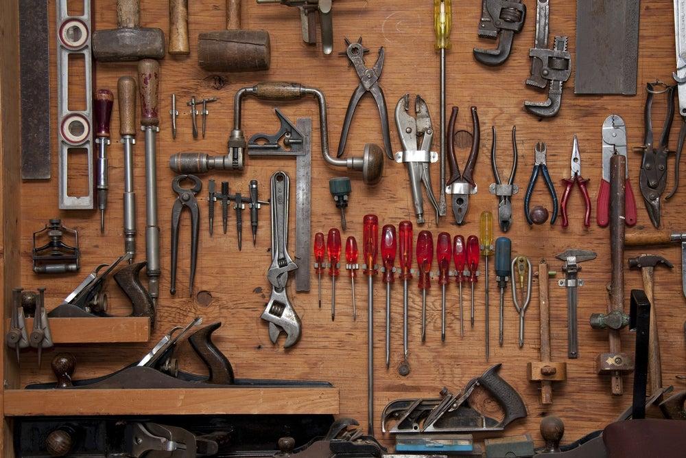Herramientas ordenadas en una pared de madera.
