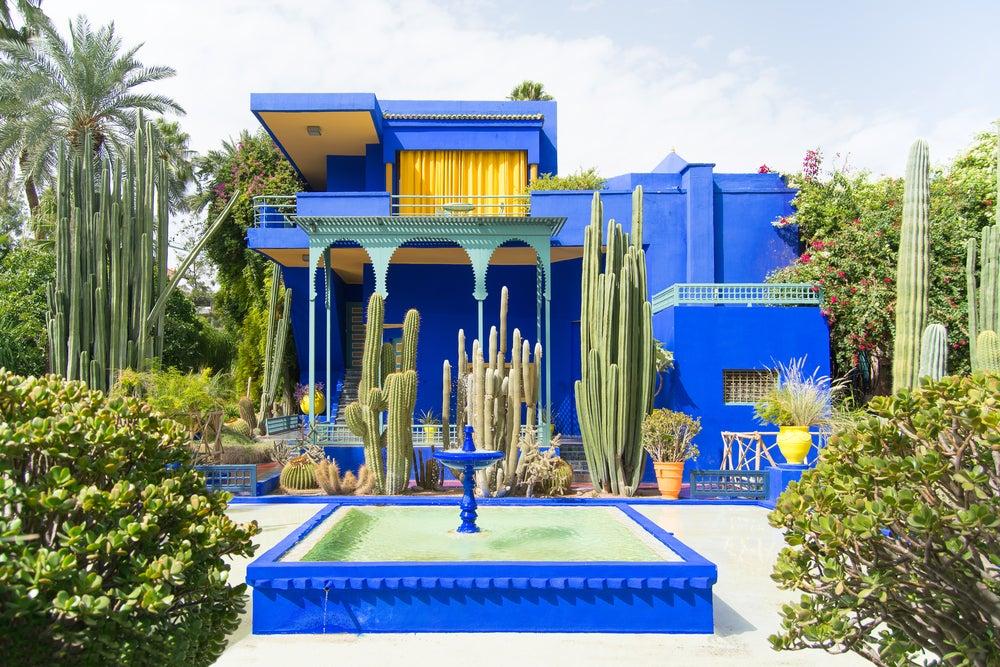 Casa de color azul en contraste con el jardín verde.