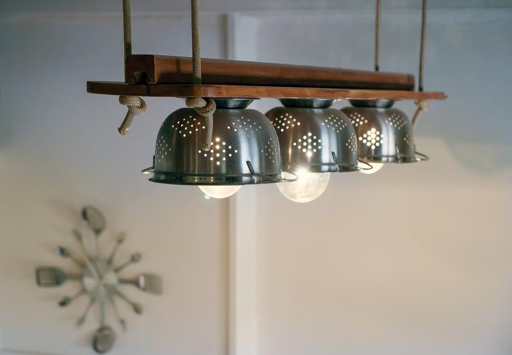 Lámparas trifásicas con forma de farolillo metálico para una cocina de madera