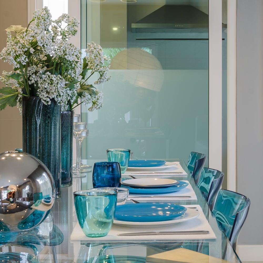 Mesa comedor de cristal con sillas transparente en color azul.