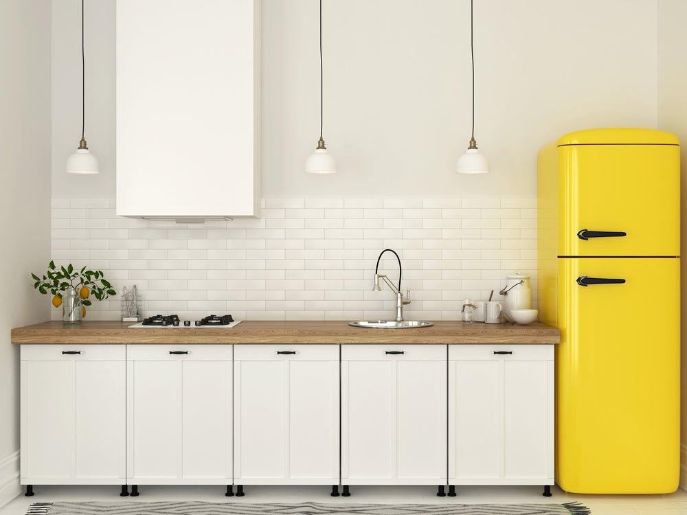 Nevera amarilla en cocina blanca.