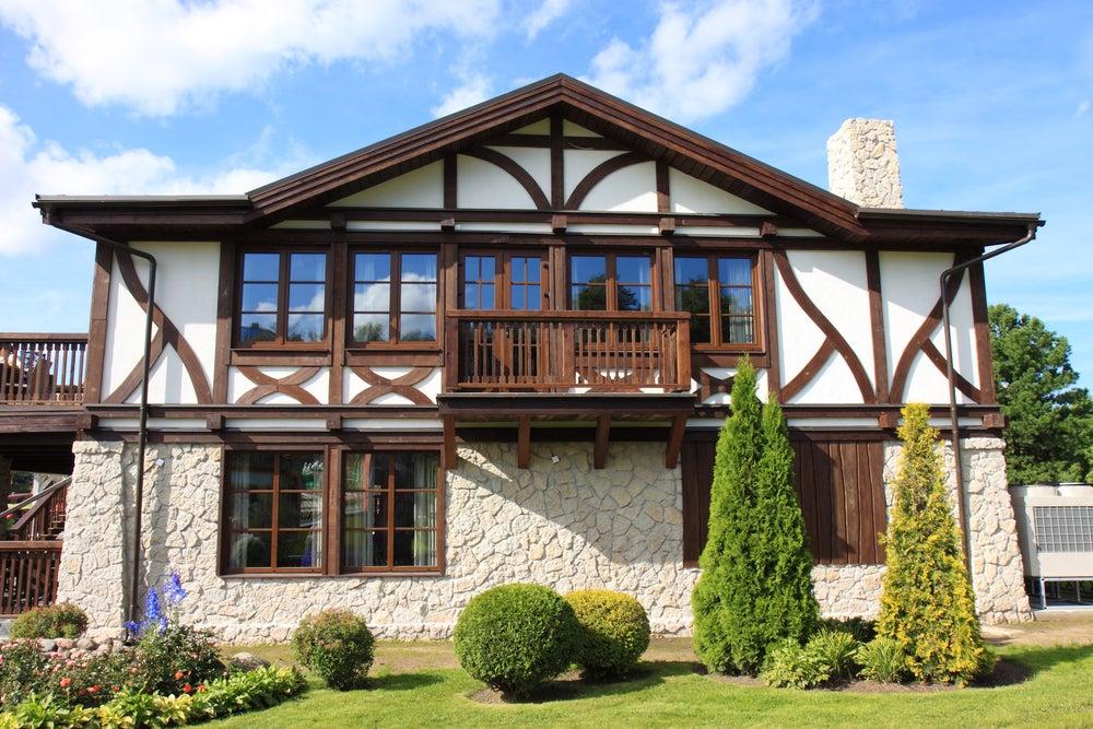 Fachada de piedra combinada con mortero en la planta baja y en la planta superior madera combinada con mortero.