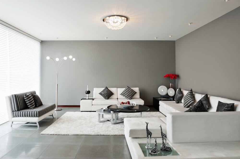 Paredes del salón en gris claro combinado con sofás en blanco y alfombra de pelo blanco.