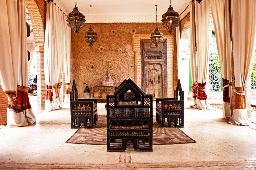 Terraza típica marroquí en colores tierra, arco de herradura, farolillos, madera.