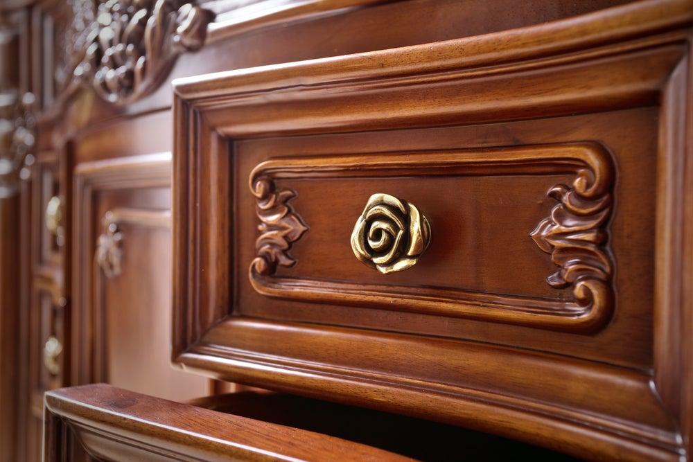 Tirador dorado con forma de rosa para un armario de madera vintage.