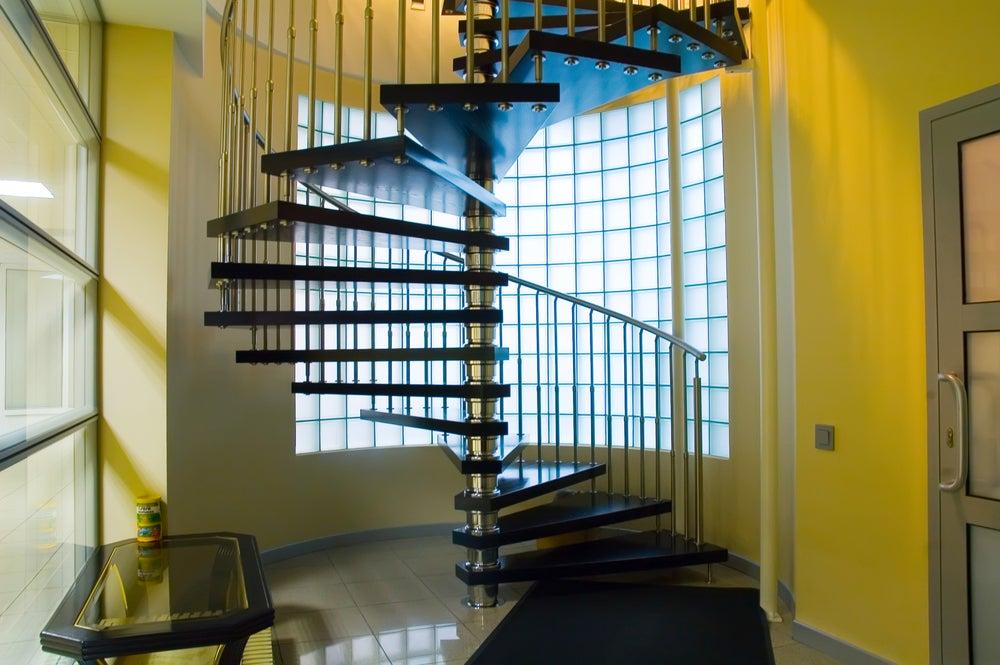 Escalera de caracol con barandilla de barrotes verticales metálicos.