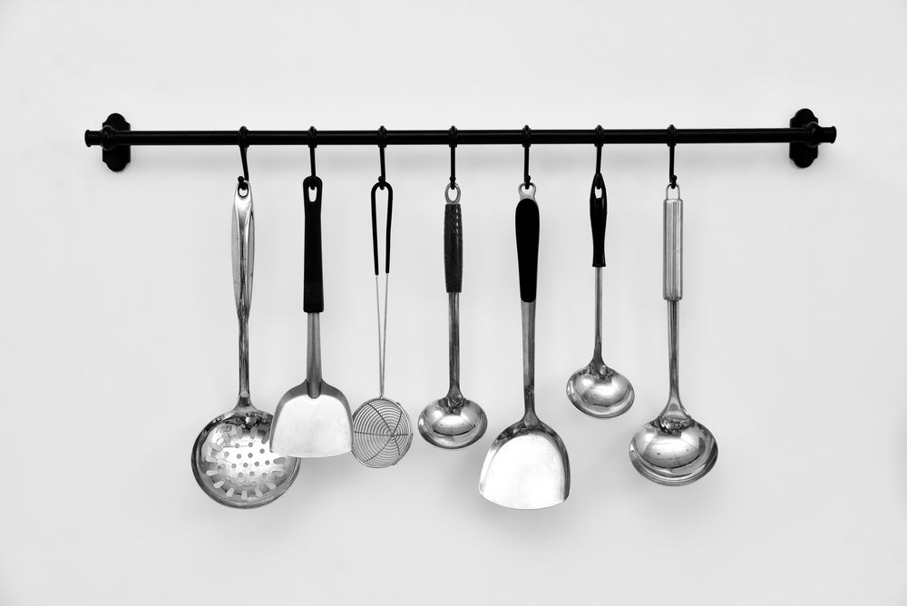 Barra metálica para colgar los utensilios de la cocina.
