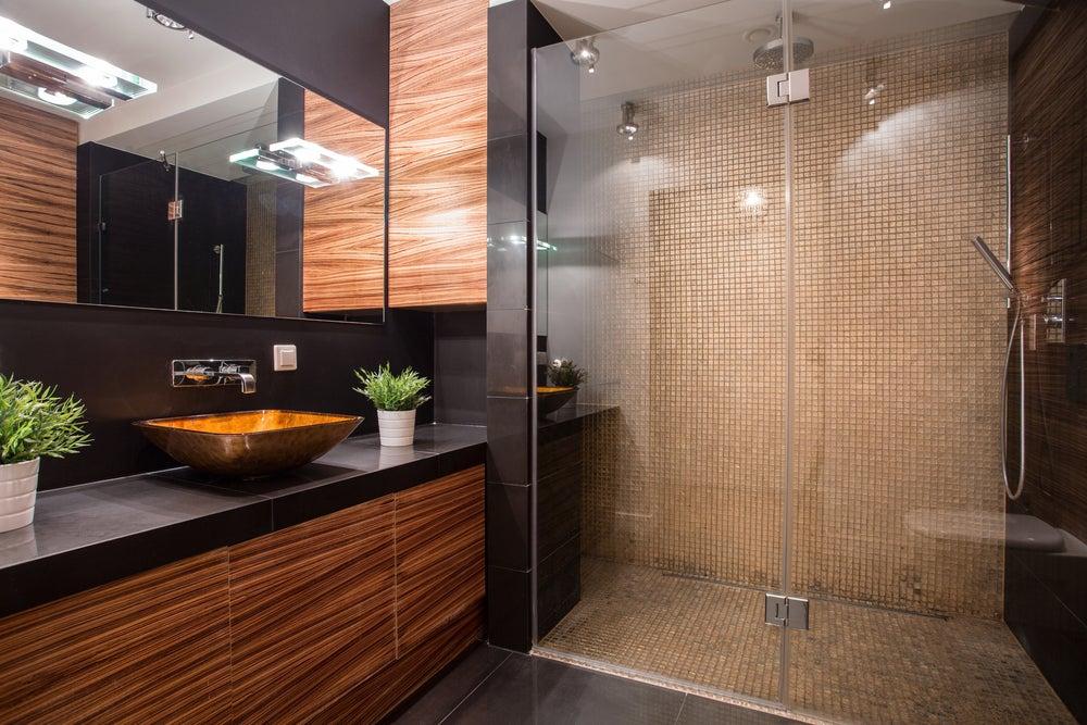 Conjunto de mueble para el baño: lavabo, cajoneras debajo de madera y espejo en la parte superior.