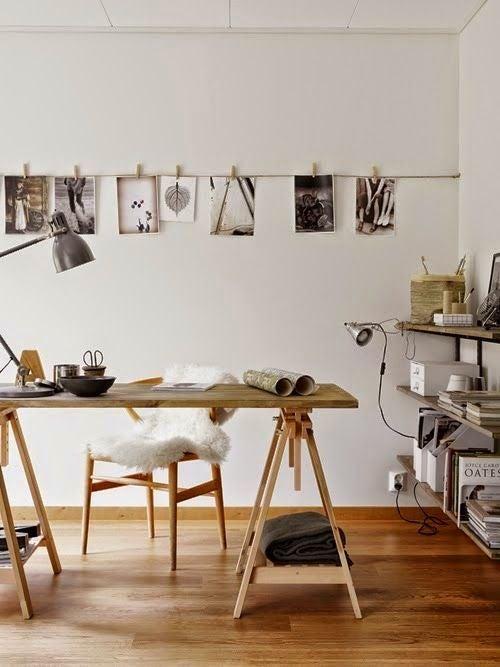 Fotos colgadas con pinzas sobre una cuerda pegada a la pared.