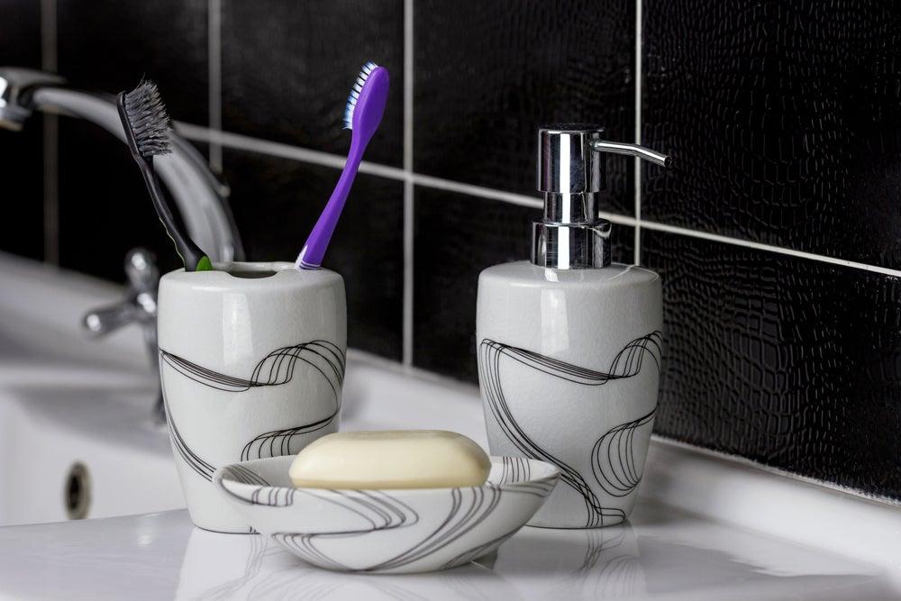 Conjunto para el baño de jabonera con cepillo de dientes y su correspondiente vaso.