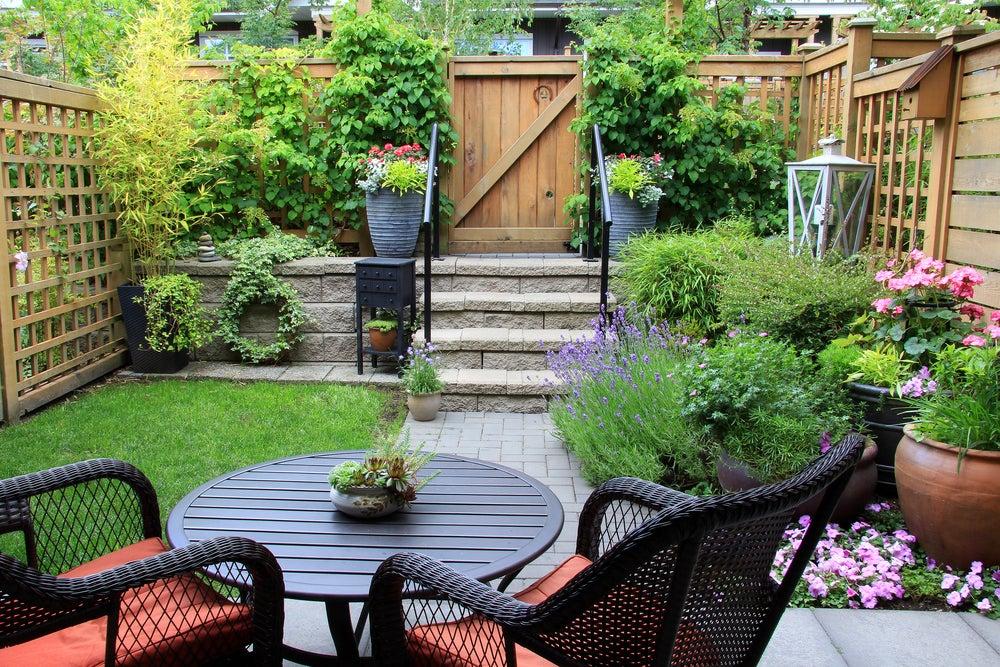 Jardín pequeño distribuido en zonas: zona de descanso y zona de macetas y plantas.