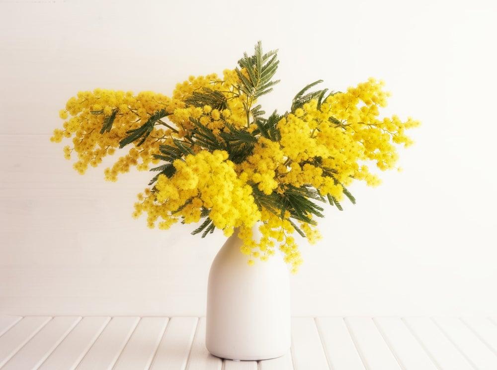 Jarrón de cerámica lacado en blanco de cuello estrecho con flores amarillas.