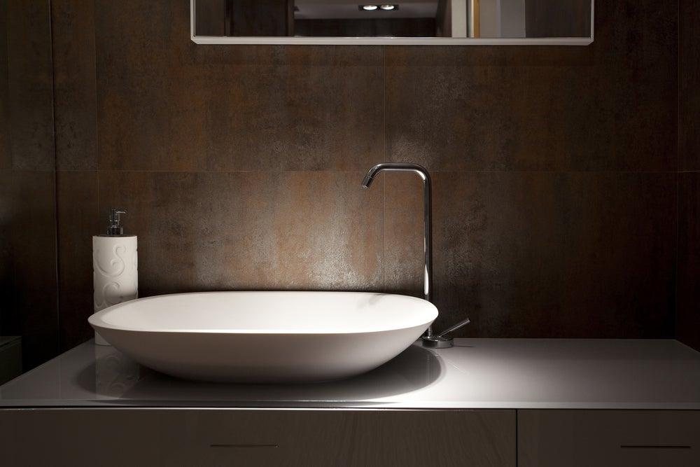 Lavabo blanco ovalado y minimalista con encimera negra.
