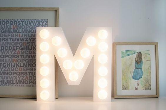Letra M de cartón con luces LED.