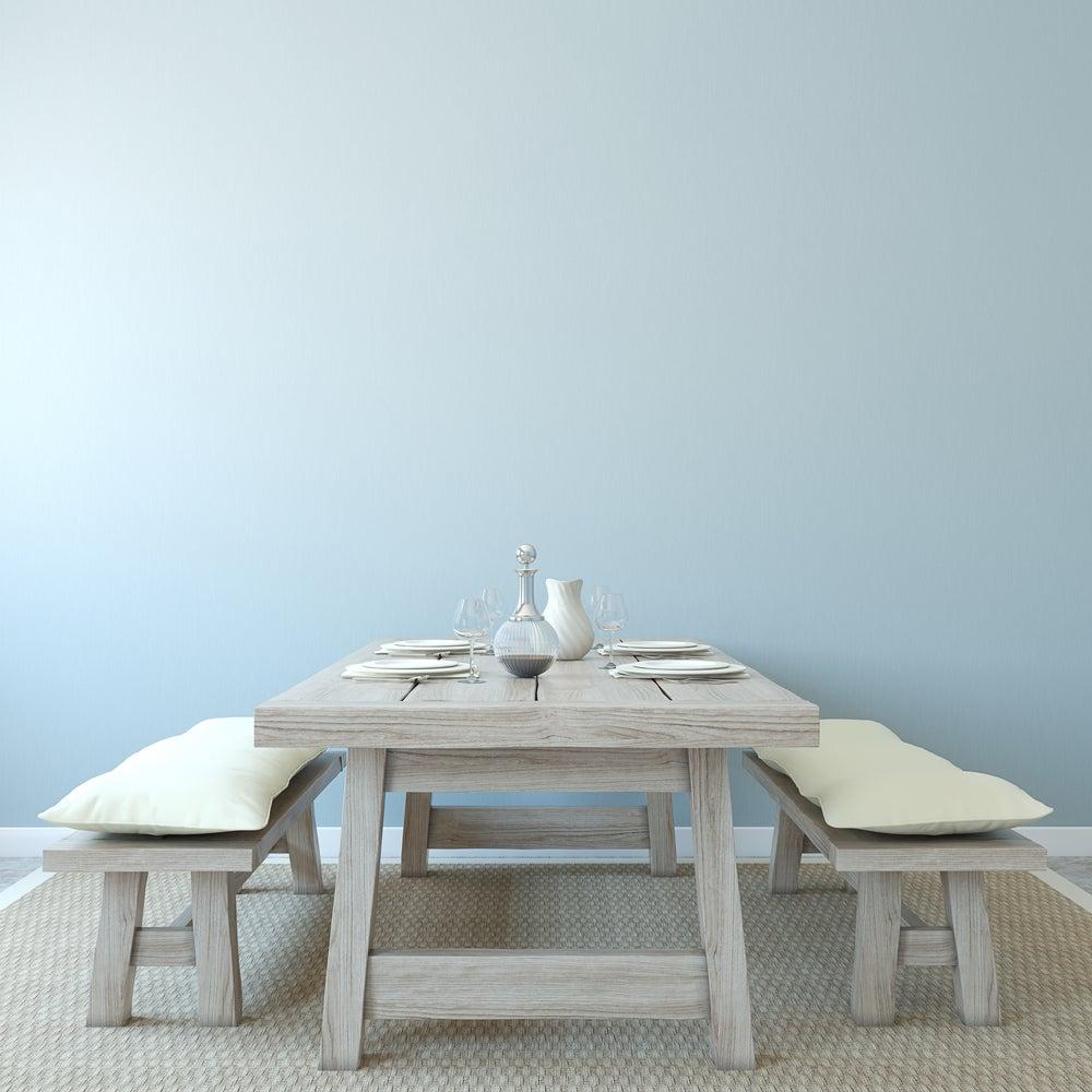 Mesa comedor rústica de colores grises con bancos de madera con cojines en blanco.