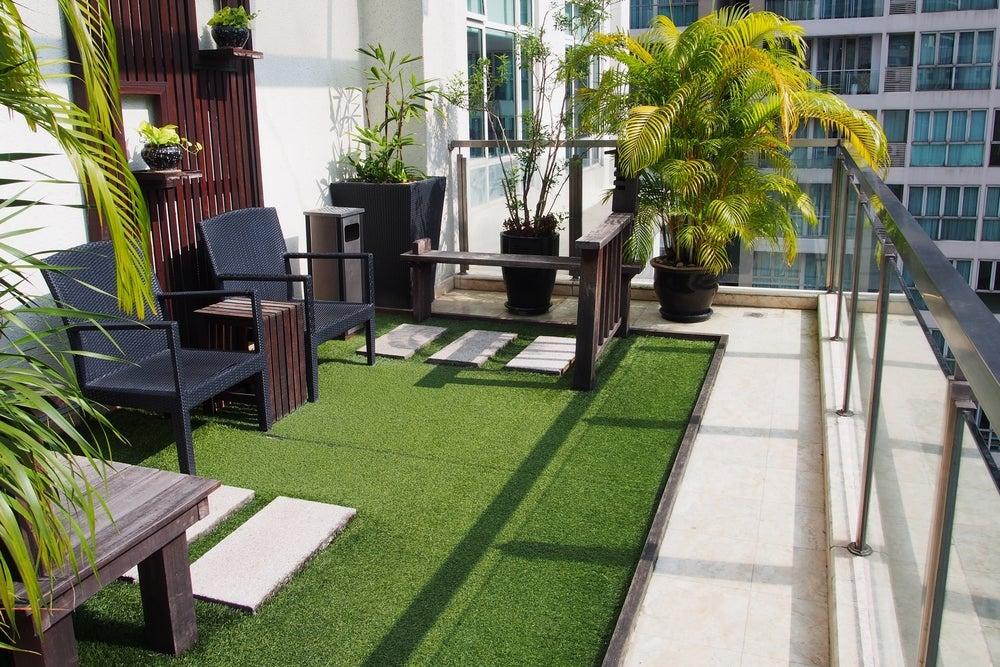Balcón decorado con plantas, césped artificial y mobiliario.