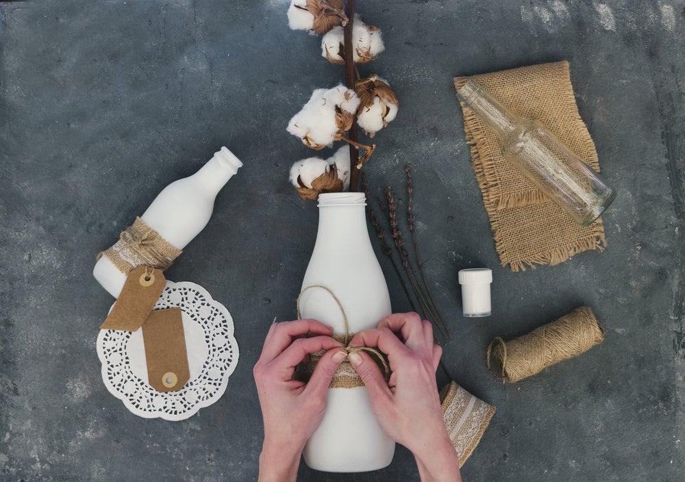 Jarrones DIY hechos con botellas de cristal pintadas en blanco.