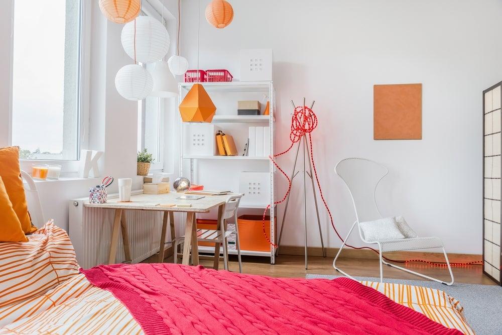 Habitación juvenil decorada en tonos naranjas.
