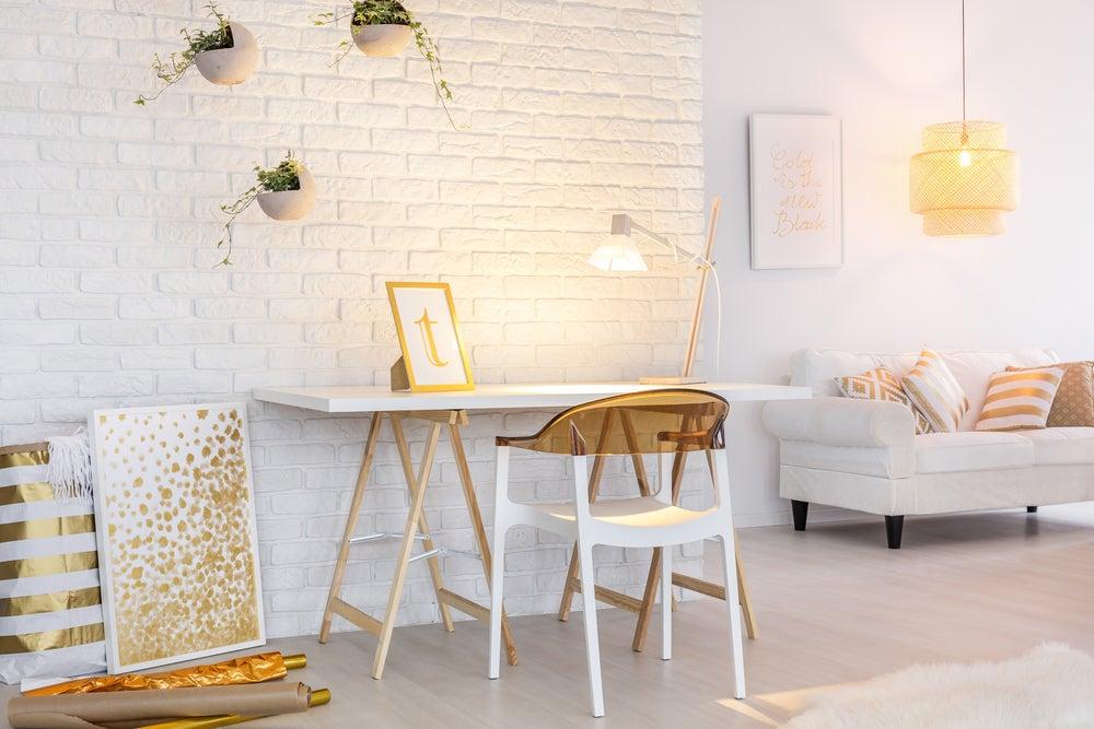 Mobiliario dorado combinado con madera y ladrillo blanco.
