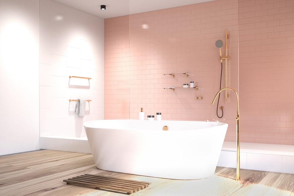 Baño con una pared rosa.