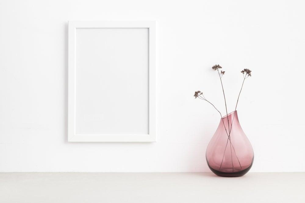 Jarrón transparente de cristal rosa con flores dentro.