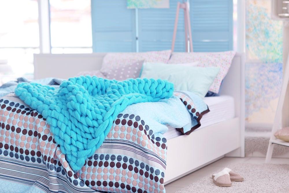 Plaid de lana azul sobre cama.