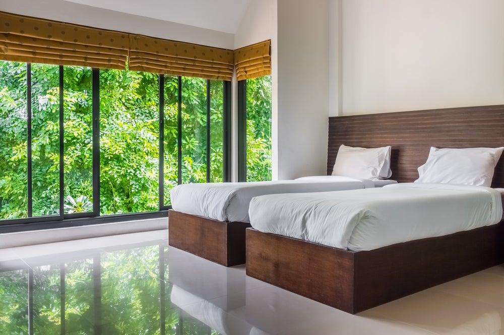 Cerramiento con cortinas de cristal en dormitorio.