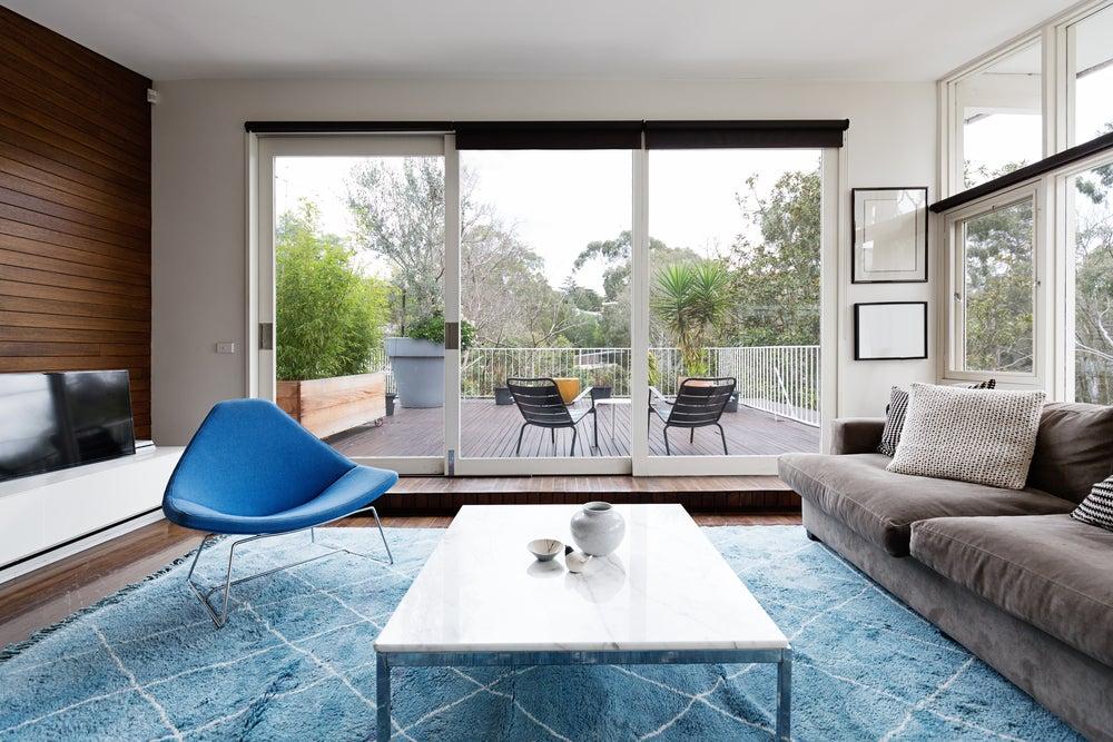 Salón Mid Century en tonos grises y azules.