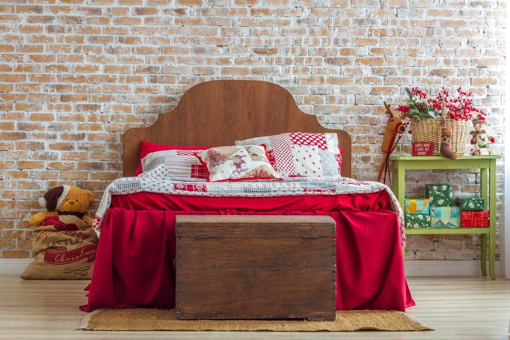 Baúl de madera al pie de cama.