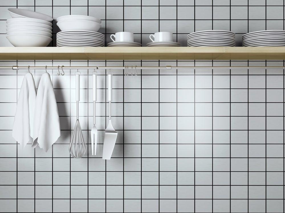 Utensilios de cocina frente a pared con azulejo blanco