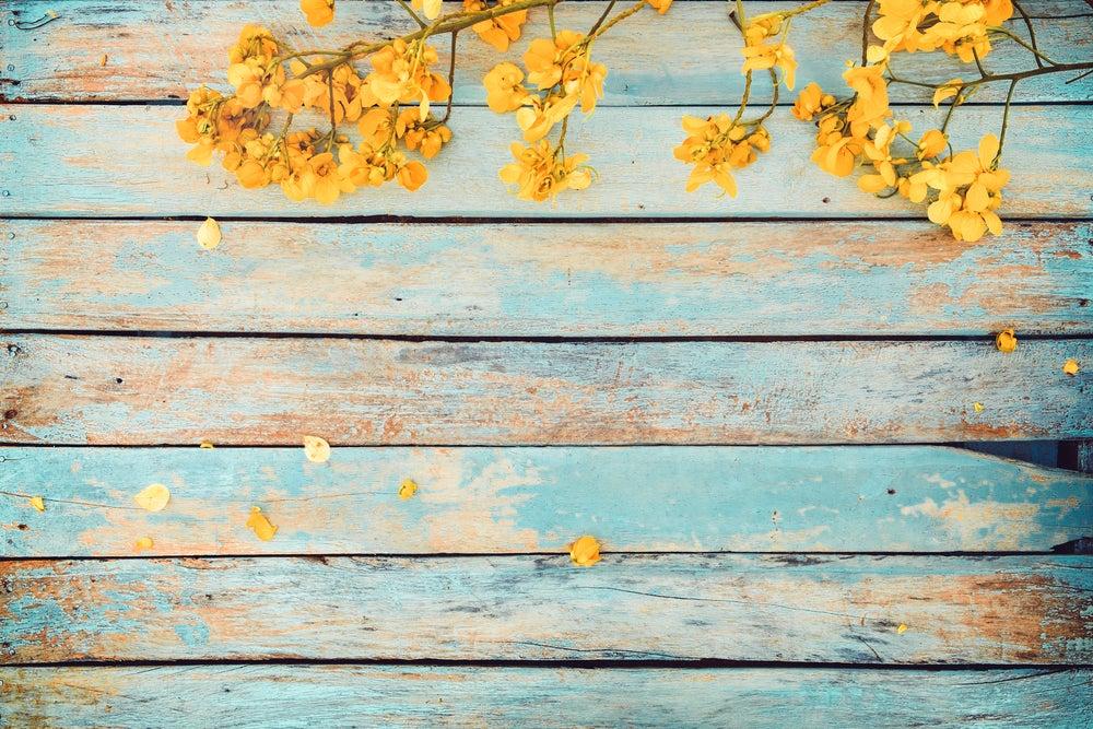 Madera desgastada en color azul con flores amarillas