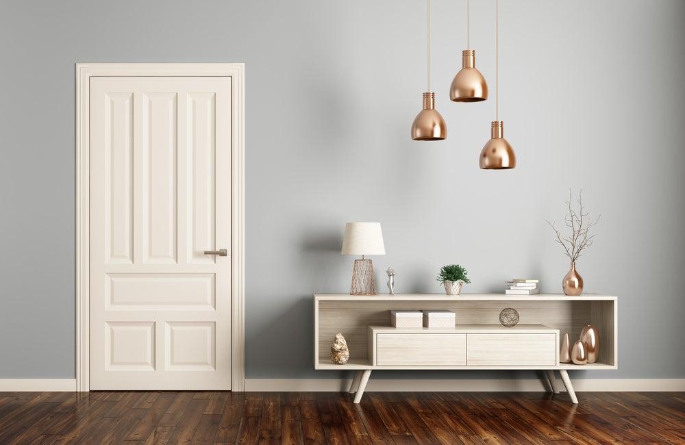 recibidor minimalista en blanco y cobre