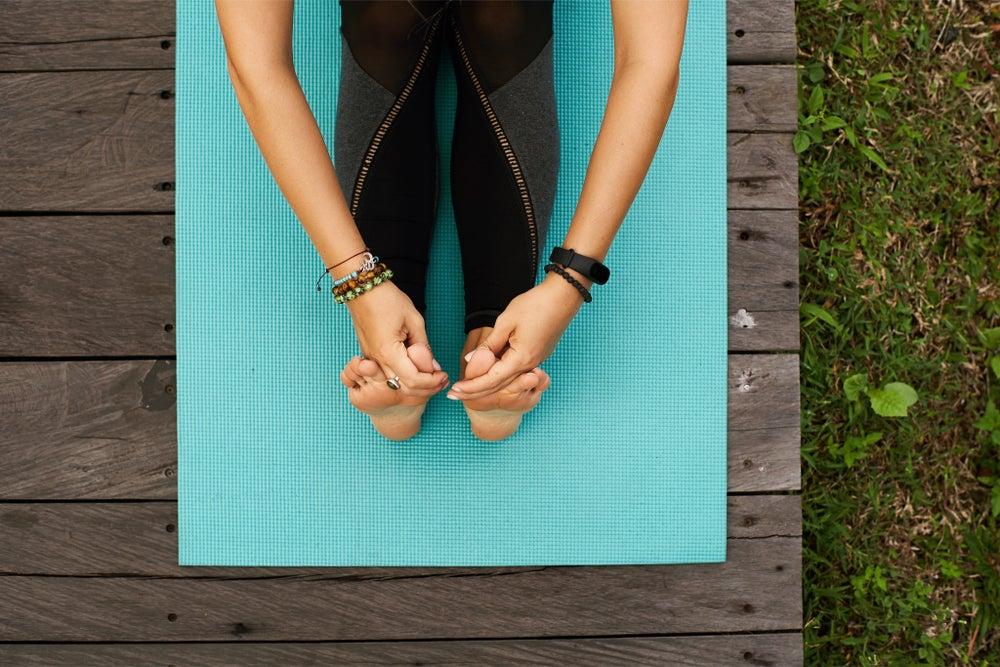 mujer en esterilla de yoga en jardín