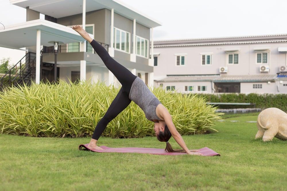 mujer haciendo yoga en el jardín