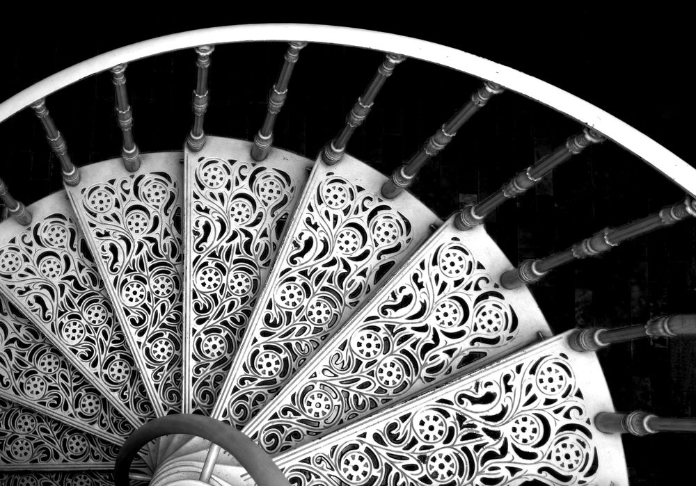 An ornate metal spiral staircase with elegant arabesques.