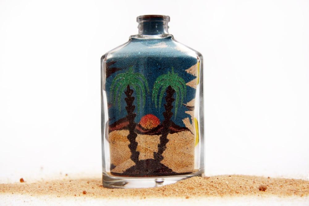 Bote de arena con imagen de oasis.