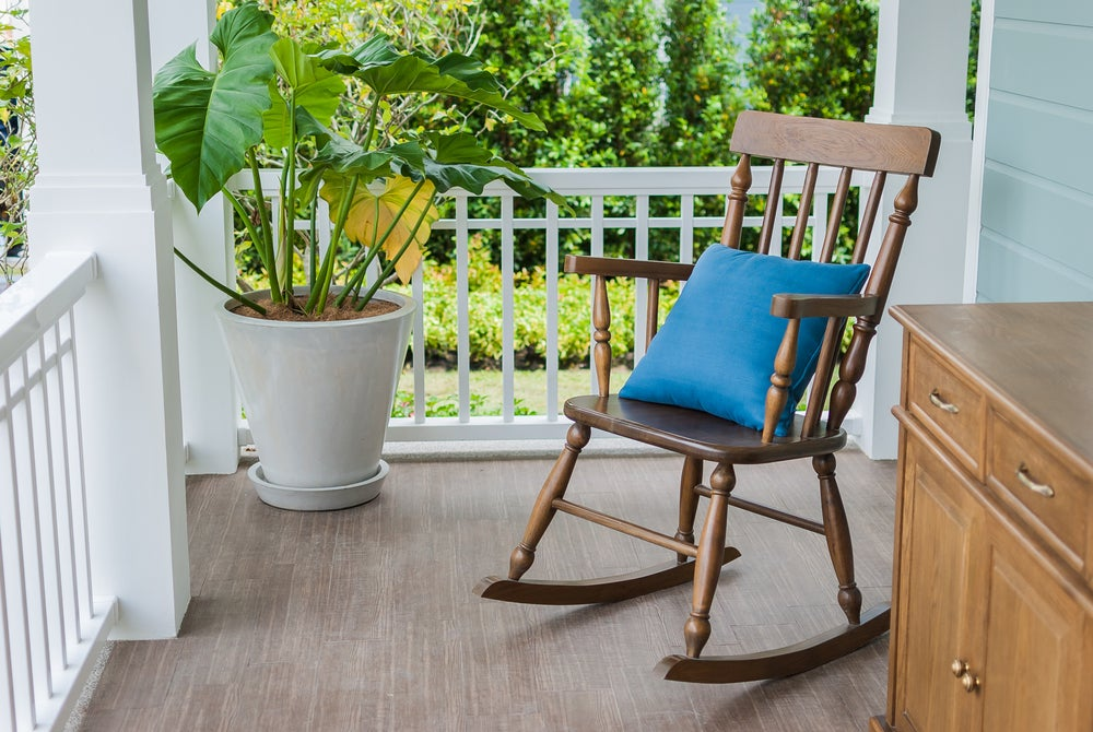 A wooden rocking chair on a porch.